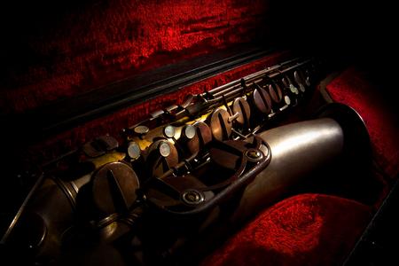 Alt-Saxophon in einem Fall mit rotem Hintergrund Standard-Bild - 54328620