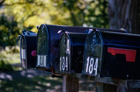 Four Mailboxes in a Row with Numbers and a Red Flag