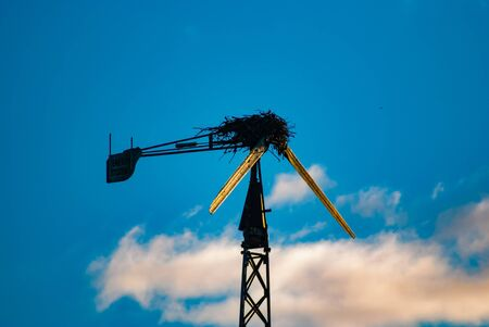 A broken down wind turbine has a massive birds nest built into the top.