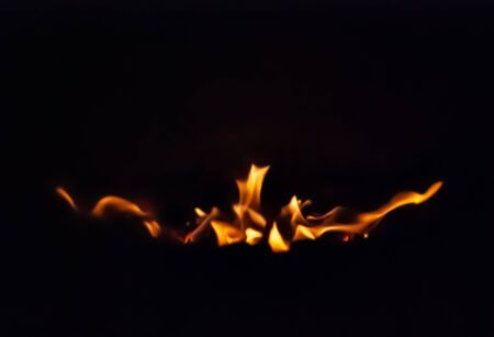 Flames are caught against a black background spreading out from a central source.