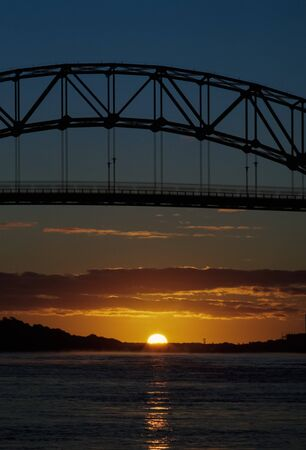 A silhouette of Sagamore bridge to Cape Cod with a low sun split by the horizon