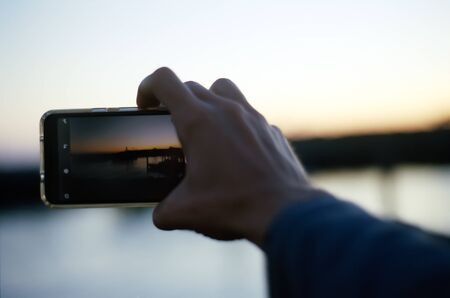 A hand extends out toward a sunrise in focus with a cell phone in the foreground, and is ready to take a picture of the horizon which is blurry in the background. Stock Photo