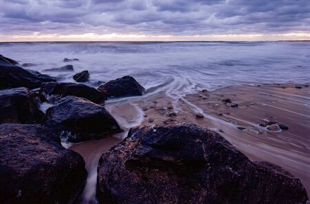 Long Exposure of the Waves Receding through Rocks 스톡 콘텐츠