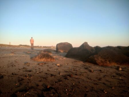 A Man Stands on a Beach with A Rocky Jetty in the Foreground 写真素材