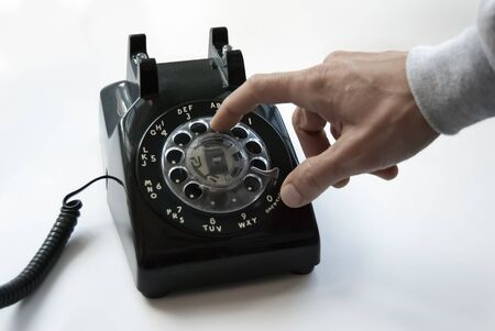 A Hand Dials an Old Rotary Phone