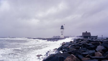 Scituate lighthouse and the jetty on a rainy day Standard-Bild