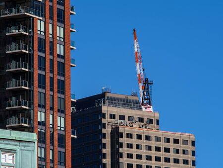 A Crane sits atop a skyscraper in downtown Boston Stock Photo