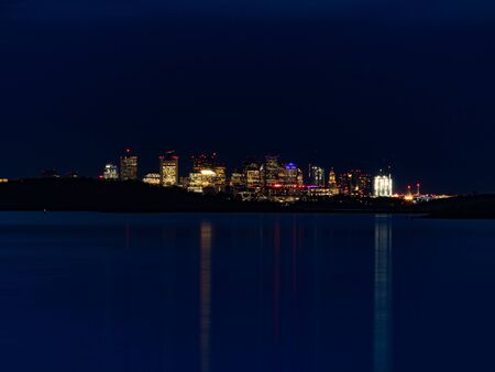 Tall city buildings twinkle at night and reflect off the still water. Reklamní fotografie