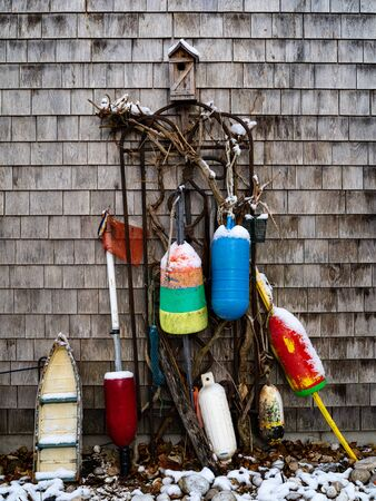 A still life of buoys and a birdhouse with some rocks and snow in the winter time.