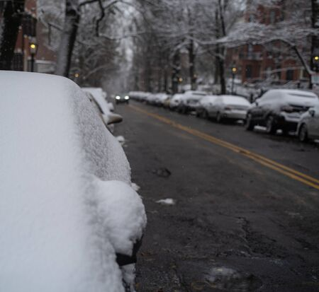 A car in the foreground with a blanket of snow over it from a heavy snowfall.