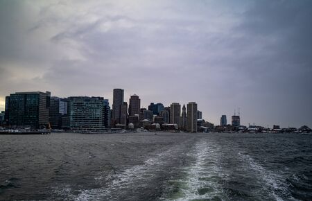 City buildings in the background with the sea in the foreground on a gloomy day in winter.