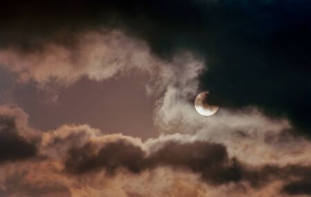 The round sun behind cloud cover with a dark and scary sky.