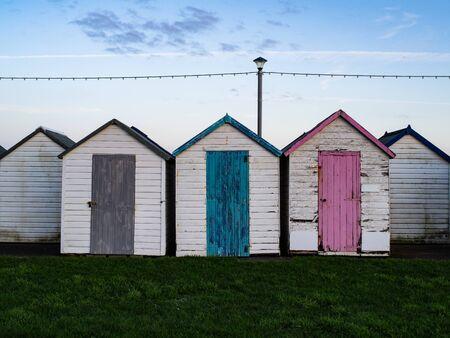 Herbe verte riche et maisons de bateau blanches avec des portes colorées et un ciel bleu.