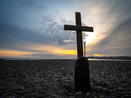 Religious symbolism on a beach with the sea in the background.