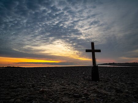 Epic sky and wooden cross in silhouette on a stone beach with colors and sea in the background.