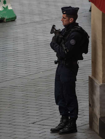 Toulouse France, January 29th, 2020, A uniformed policeman stands guard at a central square with a rifle. Editorial