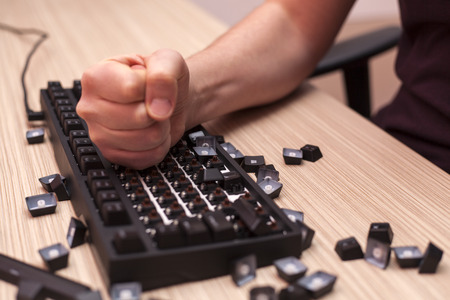 Man smashes a mechanical computer keyboard in rage and anger with his fist Foto de archivo
