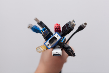 Hand holding a bunch of computer cables with different connectors Stock Photo