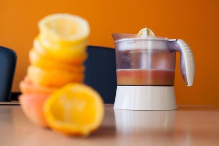 Electric juicer full of fresh citrus juice with a pile of squeezed citruses out of focus