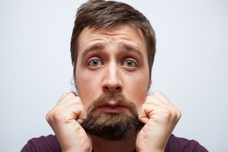 Young bearded man pulling at his long messy beard in frustration and stress