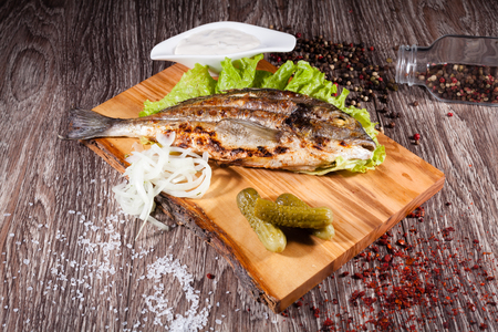 Grilled sea bream on a wooden board and lettuce, tartar sauce wi Stock Photo