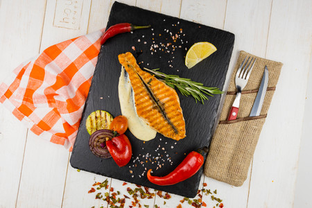 Delicious salmon steak , rich in omega 3 oil, with aromatic herbs and spices with a lemon, tomato, garlic on black background. Healthy and diet food.