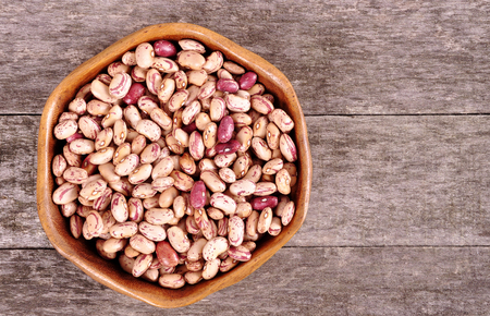 Colored beans in a wooden bowl on an old wooden background