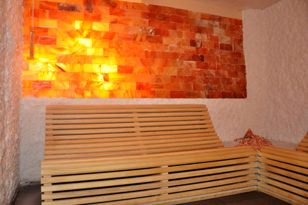 Wooden bench salt wall and headrest support in sauna room as relaxation concept