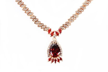 gold necklace with red crystals on a white background