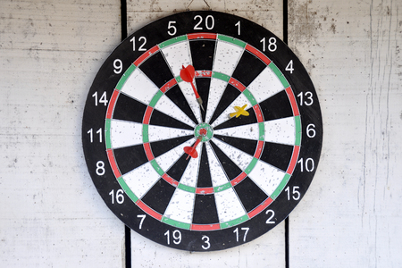 Dartboard hang on painted white color wood wall.