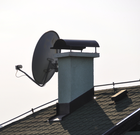 Satellite antenna installed under the roof of a country house.