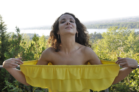 young happy curly dark-haired girl in a yellow dress with bare shoulders