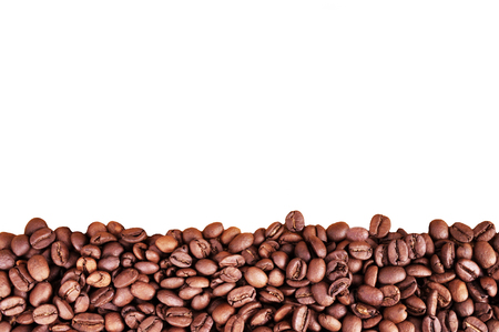 Coffee beans at border of image with copy space for text. Coffee background or texture concept. Coffee beans on white background
