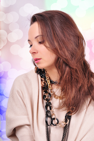 young beautiful brunette woman jewelry on abstract background. Banco de Imagens