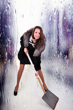 extravagant woman in a half hem with a shovel for snow removal on an abstract background. Reklamní fotografie