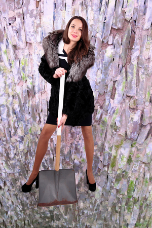 extravagant woman in a half hem with a shovel for snow removal on an abstract background Reklamní fotografie