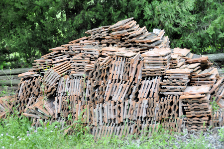Stacks of old roof tiles in a yard.