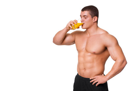 Handsome young muscular sports man drinking juice isolated on white background photo