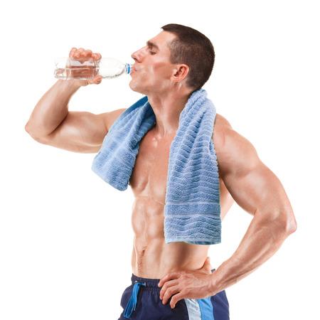 Jonge gespierde man met blauwe handdoek over de nek, het drinken van water, geïsoleerd op een witte achtergrond Stockfoto