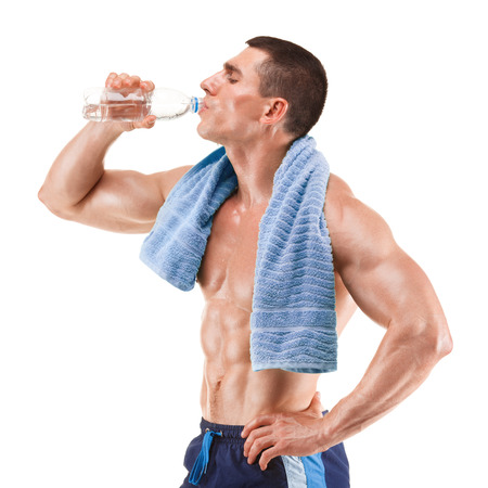 Young muscular man with blue towel over neck, drinking water, isolated on white background
