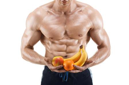 Shaped and healthy body man holding a fresh fruits, shaped abdominal, isolated on white background, colored retouched
