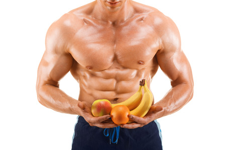 bicep: Shaped and healthy body man holding a fresh fruits, shaped abdominal, isolated on white background, colored retouched