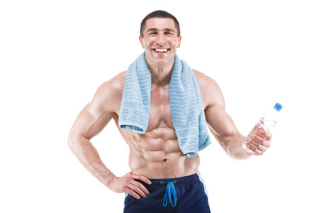 appease: Young muscular man smiling with blue towel over neck, drinking water, isolated on white background