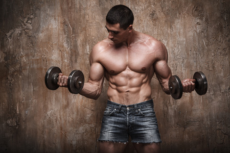 Handsome muscular man working out with dumbbells on wall background
