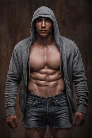 근육 질의 가슴과 복근을 드러내는 열린 재킷을 가진 근육 질의 젊은 남자.