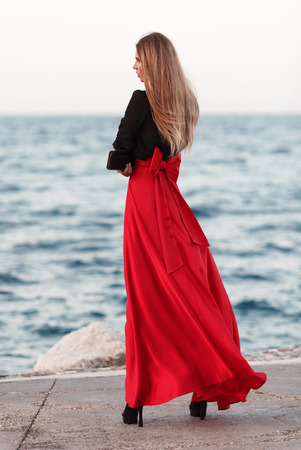 fluttering: Sexy young beauty woman in fluttering red dress at the coast. Fashion woman Stock Photo