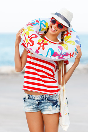 Beach woman happy and colorful wearing sunglasses and beach hat having summer fun during travel holidays vacation. Stockfoto