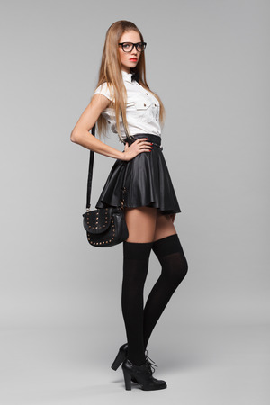 Beautiful woman is in fashion style in black mini skirt. Fashion girl