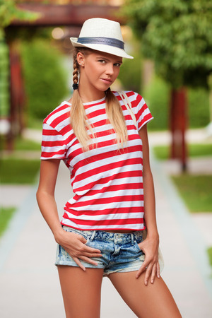 sexy shorts: Beautiful sexy female in shorts and striped t-shirt, in hat, outdoors. Tanned girl in summer.
