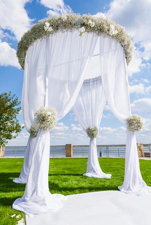 녹색 잔디밭에 결혼식 설정입니다. 웨딩 아치 스톡 콘텐츠